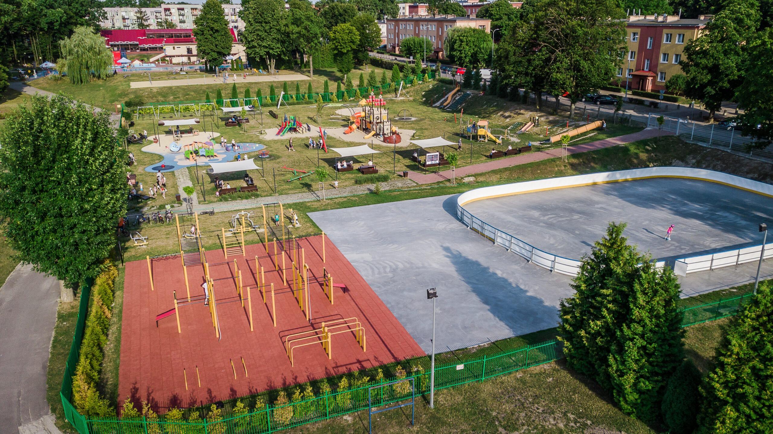 Zdjęcie przedstawia widok z drona na plac zabaw, siłownię na świeżym powietrzu oraz lodowisko przy Miejskim Ośrodku Sportu i Rekreacji