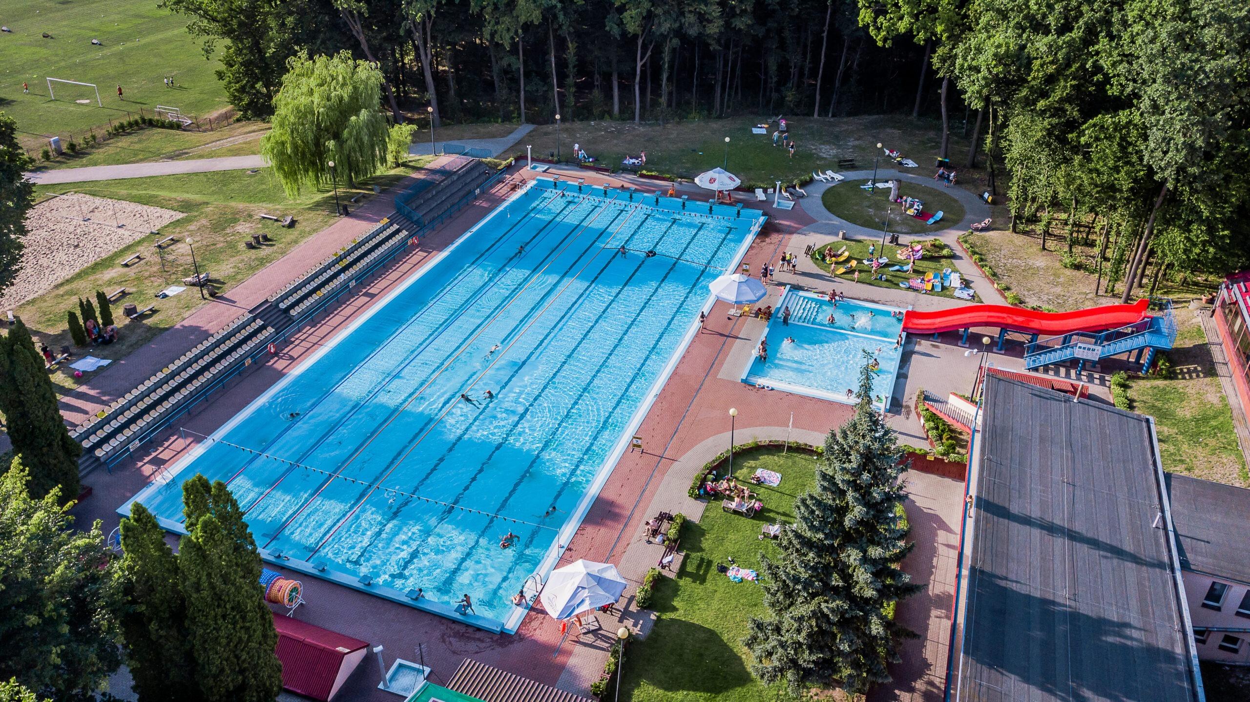 Zdjęcie przedstawia basen odkryty, brodzik oraz zjeżdzalnię Miejskiego Ośrodku Sportu i Rekreacji