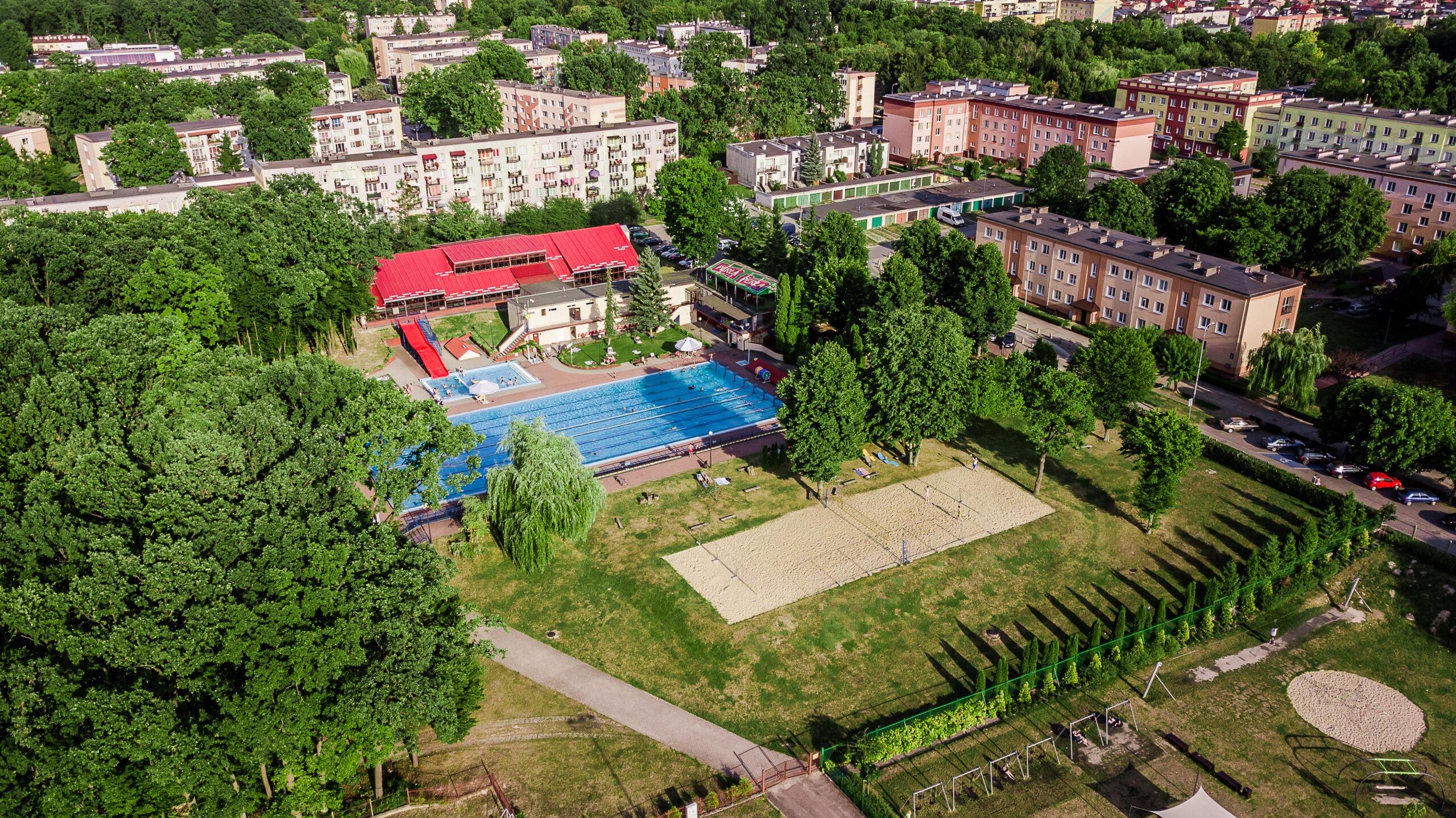 Zdjęcie przedstawia widok z drona na boisko do piłki plażowej i basen odkryty oraz budynek basenu zakrytego Miejskiego Ośrodka Sportu i Rekreacji