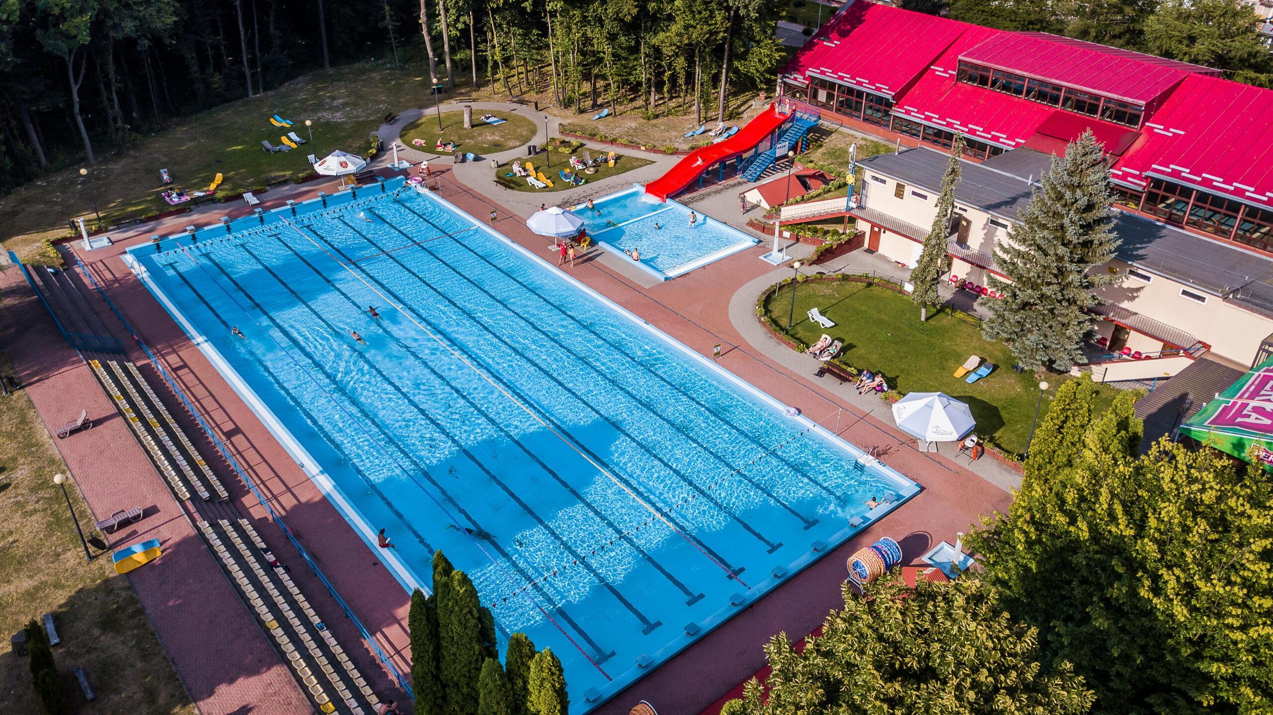 Zdjęcie przedstawia widok z drona na odkryty basen oraz budynek zakrytego basenu.