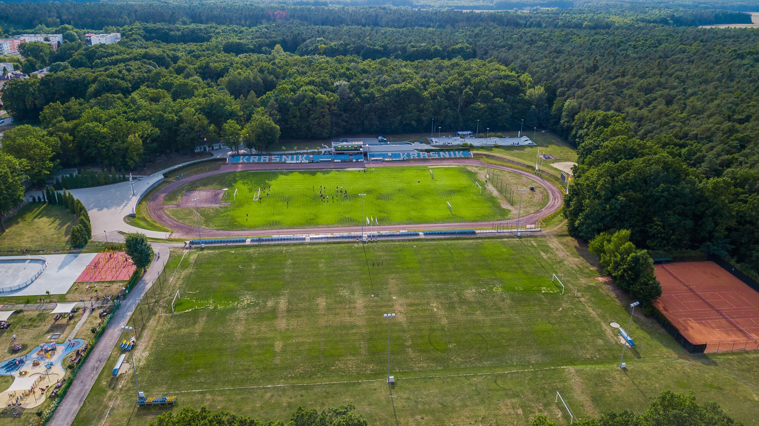 Zdjęcie przedstawia widok z drona na trzy boiska do piłki nożnej różniące się wielkością i bieżnię przy Miejskim Ośrodku Sportu i Rekreacji