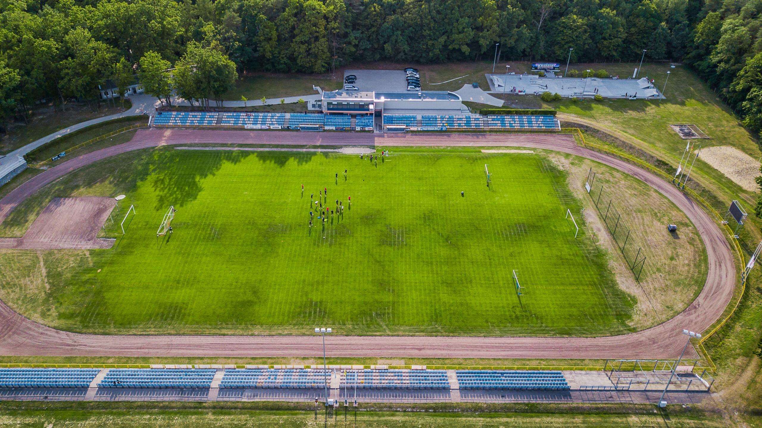 Zdjęcie przedstawia widok z drona na boisko i bieżnię przy Miejskim Ośrodku Sportu i Rekreacji