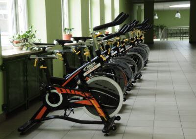 Zdjęcie przedstawia rowerki do ćwiczeń znajdujące się w na hali sportowej