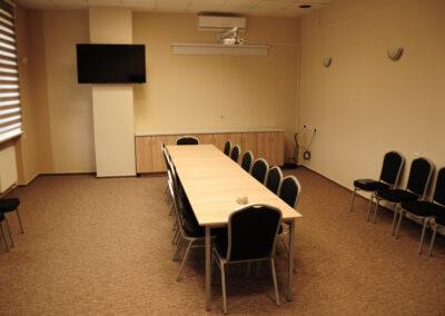 Zdjęcie przedstawia pokój konferencyjny z długim stołem projektorem i telewizorem