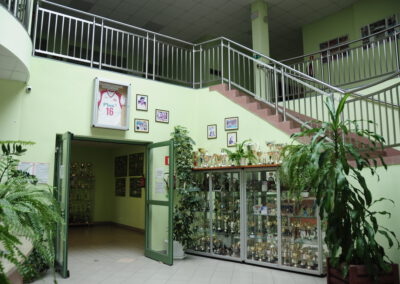 Zdjęcie przedstawia wejście na halę sportową z roślinami, schodami, witrynami z dużą ilością pucharów oraz ramki ze zdjęciami i koszulką Arkadiusza Gołasia. Tragicznie zmarłego gracza reprezentacji Polski w piłce siatkowej.