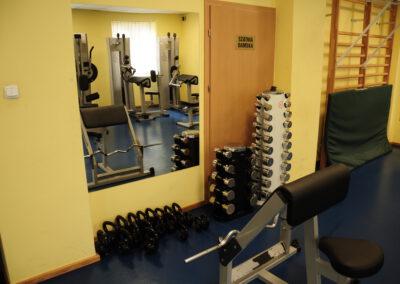 Zdjęcie przedstawa siłownię oraz znajdujące się na niej sprzęty do ćwiczeń
