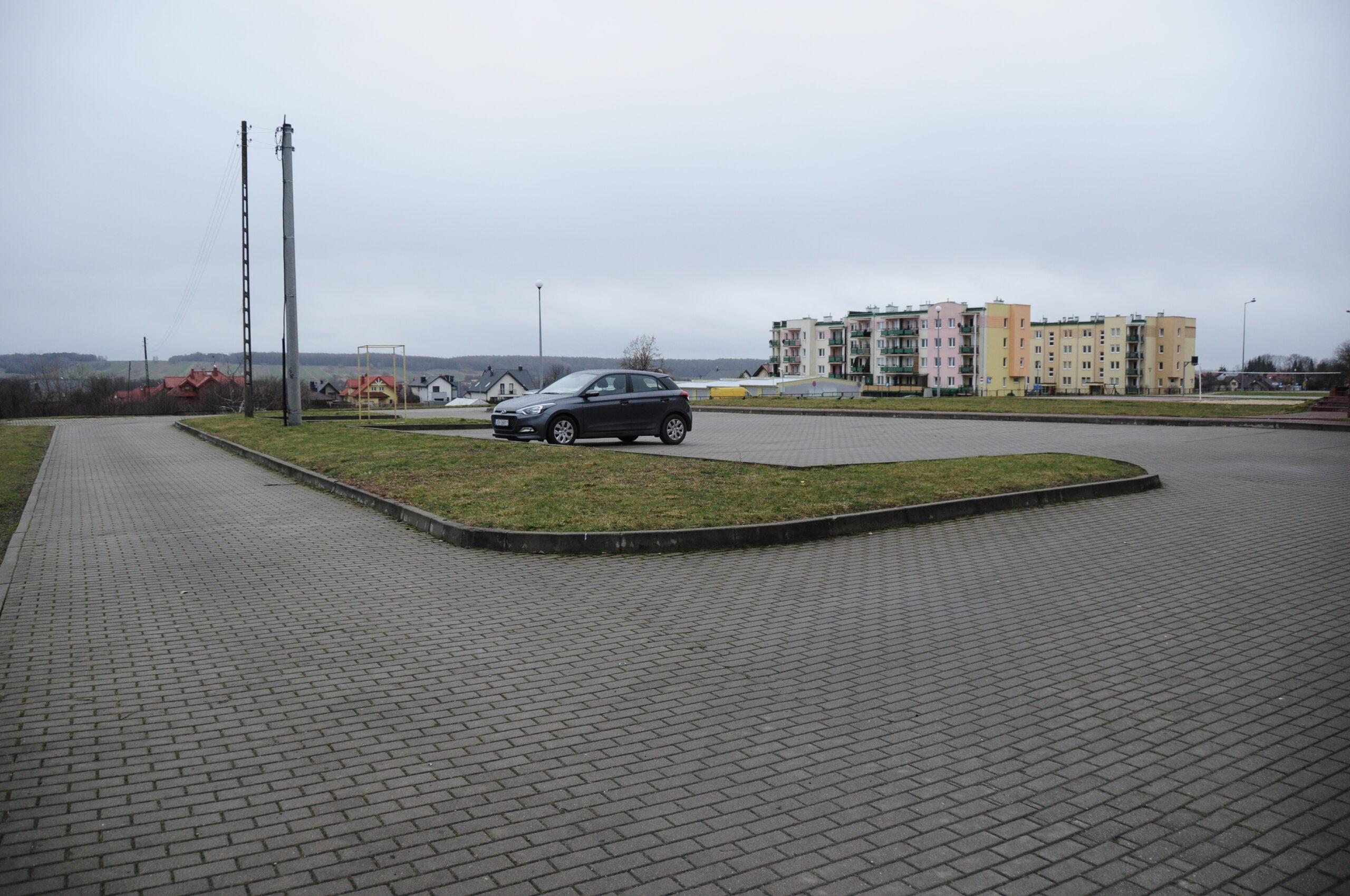 Zdjęcie przedstawia parking przy hali sportowej