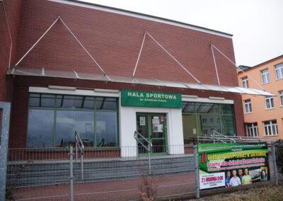 Zdjęcie przedstawia budynek, wejście z zewnątrz hali sportowej