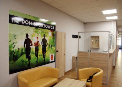 Zdjęcie przedstawia recepcję z miejscem do posiedzenia i rozmowy w głównym holu hotelu sportowca