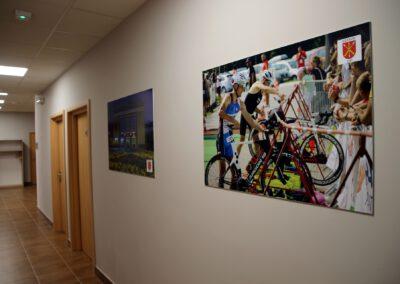 Zdjęcie przedstawia korytarz w hotelu sportowca i wiszące tam obrazy